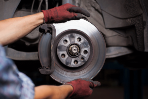 Technician is positioning a new disc brake. Brake noise from your vehicle may mean it is time to invest in a new set of brakes